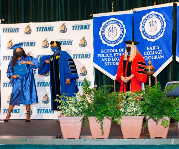 President Williams bumps elbows with a recent graduate on stage. Both are wearing face masks and blue graduation regalia.