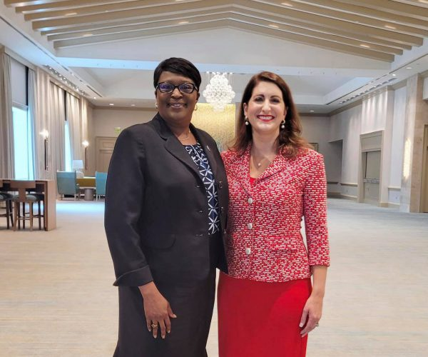 SPC President Dr. Tonjua Willams and Dr. Angela Garcia Falconetti, President of Polk State College and Chair of FCS Council of Presidents pose standing next to each in a conference room.