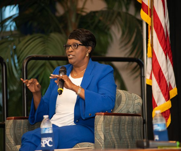 SPC President Dr. Tonjua Williams, dressed in a blue suit and seated on stage in front of an American flag, speaks to an audience at the Greater Seminole Area Chamber of Commerce luncheon held in June 2021.