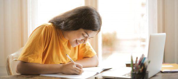 Woman in a yellow shirt writing