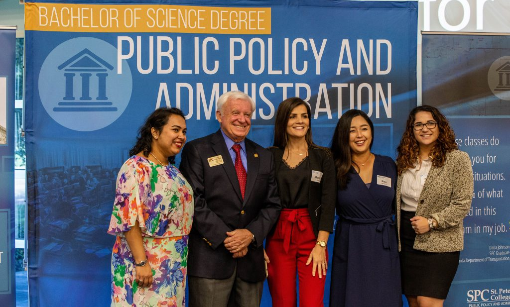 """Professor Kronschnabl poses with four female students in front of a sign reading """"public policy and administration"""""""