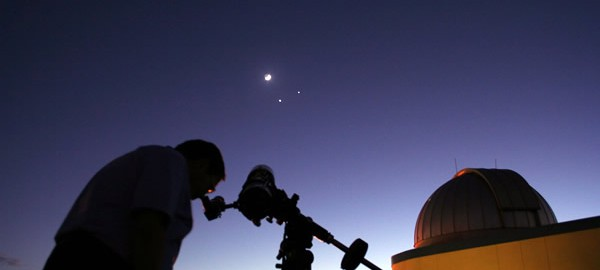 photo of man using telescope at SPG Planetarium