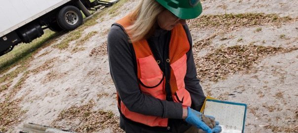 Melinda Hamsher examines clay from water sampling well.